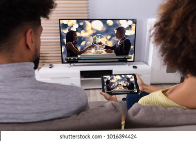 Young Couple Sitting On Sofa Connecting Television Channel Through WiFi On Digital Tablet
