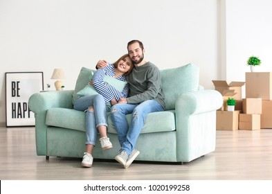 Young couple sitting on sofa after moving to new home