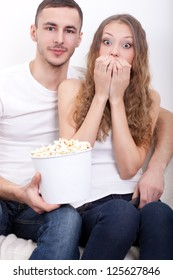 young couple sitting on the sofa eating popcorn and watching  tv, girl scared