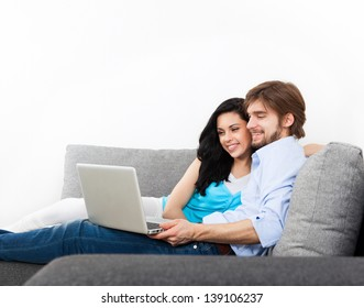 young couple sitting on a sofa happy smile, using laptop, portrait of lovely young man and woman hug, embrace on the couch, with cope space