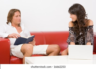 Young couple sitting on the sofa at home, he reads a book, she works  with the laptop
