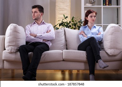 Young couple sitting on the sofa after quarrel