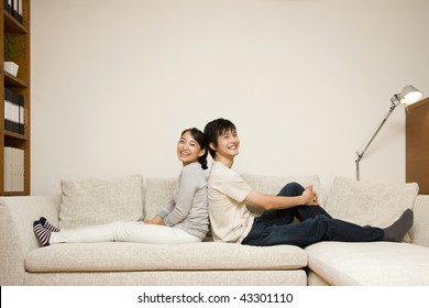 A young couple sitting on the sofa back-to-back
