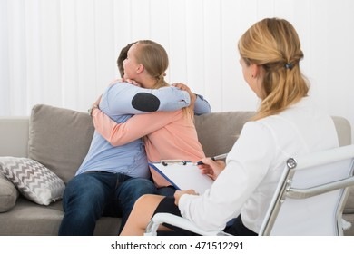 Young Couple Sitting On Sofa Embracing In Front Of Female Psychologist