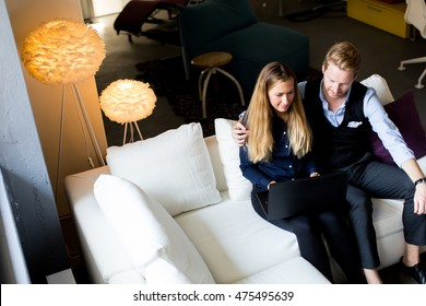 Young couple sitting on the sofa and websurfing on internet