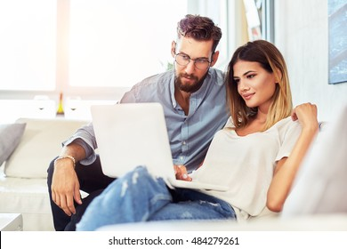 Young couple sitting on the sofa and surf the Internet