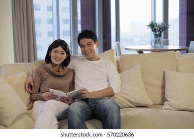 Young couple sitting on sofa reading a book
