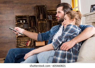 Young couple sitting on sofa and using tv remote control