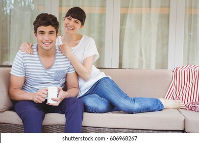 Young couple sitting on sofa and smiling in living room