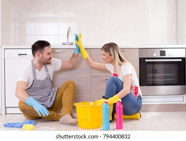 Young couple sitting on tiled floor in kitchen, satisfied after finished chores, Teamwork in housework