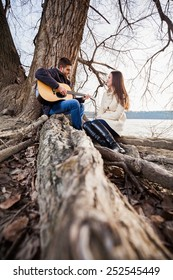 Young couple sitting on the tree, playing guitar and singing