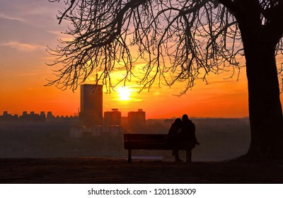 Young couple sitting on a wooden bench under a tree in Kalemegdan fortress park with romantic view of Sava river and skyline of New Belgrade with golden orange sunset in Belgrade Serbia