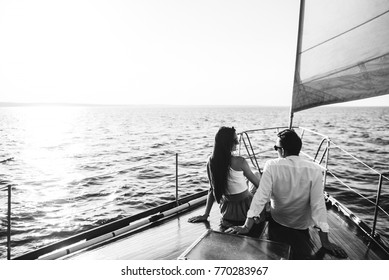 Young couple sitting on yacht and watching the sunset