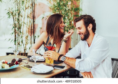 Young couple sitting in the outdoor bar and drink cocktails