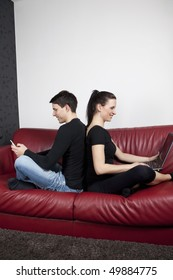 Young couple sitting an the red sofa. She works on laptop, he has mobile phone in his hand.