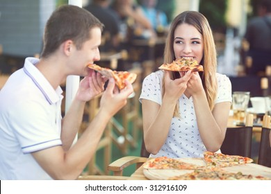 Young couple sitting in a restaurant eating pizza