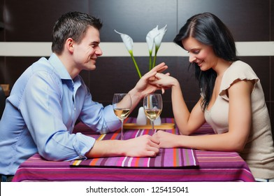 Young couple sitting in restaurant, flirting and drinking wine