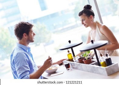 A young couple sitting at a table and have lunch at an outdoor restaurant