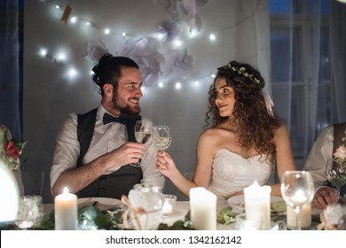 A young couple sitting at a table on a wedding, clinking glasses.