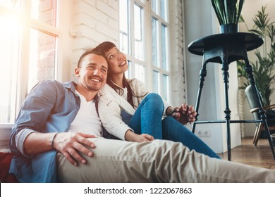 Young couple sitting together in big loft living room. Romantic relationship and domestic life
