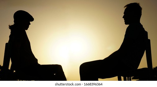Young couple sitting together on chair, looking at each other. Beautiful view of sunset. Beautiful view of sunset, sunlights and sunny day. Listening silence, meditation.