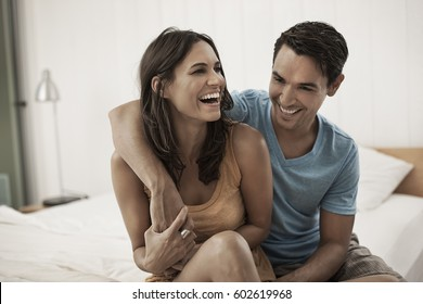 A young couple sitting together on the edge of a bed, laughing and hugging