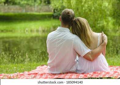 Young couple sitting together in a summer park and have a picnic on a checkered picnic blanket. You see them from behind as they hug and look at a lake.