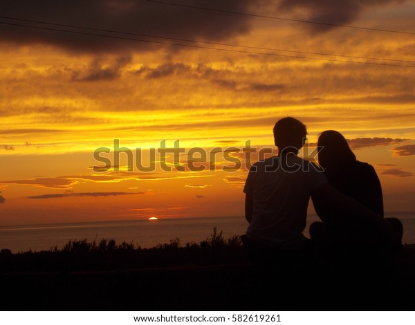 Young couple sitting and watching sundown