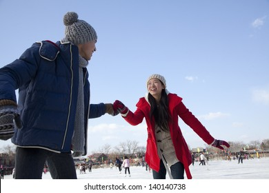 Young couple skating at ice rink