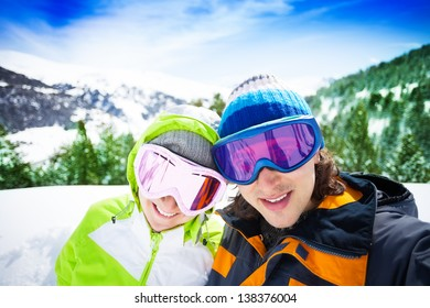 Young couple of skiers with mountains on background