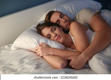 Young couple sleeping in bed at night
