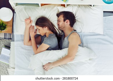 Young couple sleeping in bed under blanket