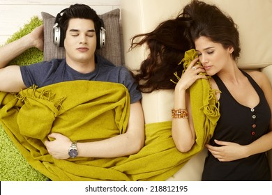 Young couple sleeping at home, girl on sofa, boy with headphones on carpet next to her.