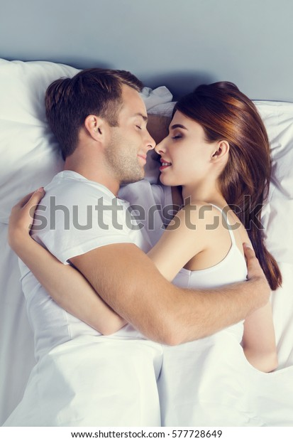 Young couple sleeping and hugging on the bed in bedroom. Caucasian models in love, relationship, dating, happy people, bedtime concept shot.