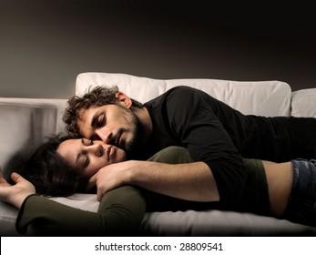 young couple sleeping on a sofa