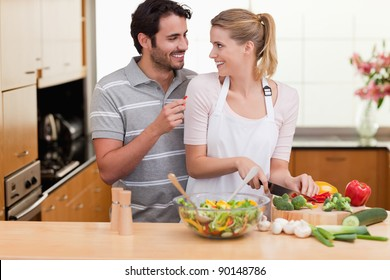 Young couple slicing vegetables in their living room