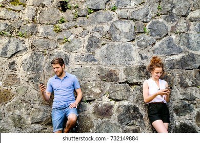 Young couple with smartphones against stone wall in town.