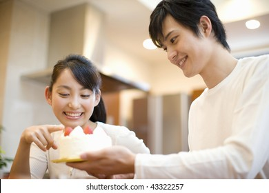 A young couple smiling and having cake