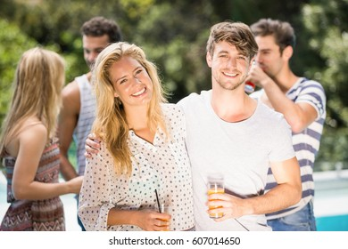 Young couple smiling and having juice together and their friends standing behind