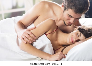 Young couple smiling and hugging on the bed in the bedroom