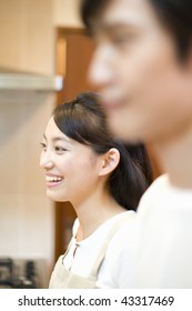 A young couple smiling in the kitchen