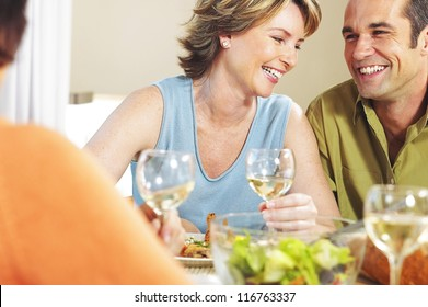 Young couple smiling and laughing while socialising with friends at dinner