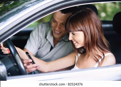 Young couple of smiling people looking to mobile phone, sitting in car.