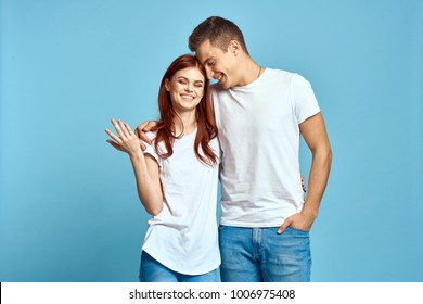 young couple smiling in a single sweater on a blue background