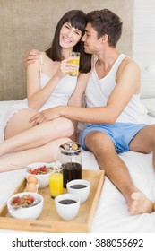 Young couple smiling while having breakfast together in bedroom