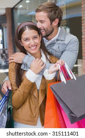 Young couple smiling while looking at the camera next to a shopping mall
