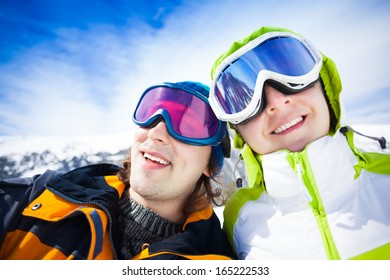 Young couple of snowboarders with mountains on background