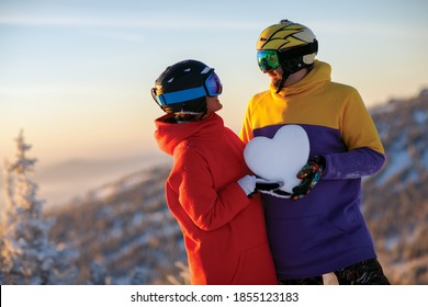 A young couple with a snowy heart in their hands against the background of a winter landscape in the ski resort. Sheregesh. Russia.