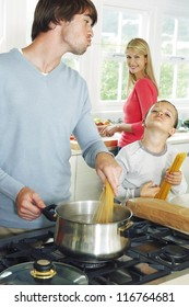 Young couple and son in kitchen cooking spaghetti.