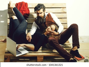 Young couple spend time together with laptop, computer. Pretty girl or beautiful woman lying on knees of handsome man, bearded hipster with beard, talking on mobile phone on wooden pallet sofa